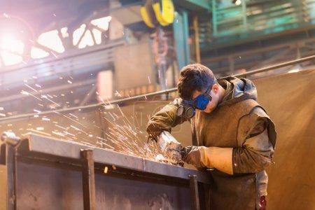 Photo pour Jeune homme avec masque de protection soudage dans une usine - image libre de droit