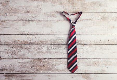 Coup de cravate colorée sur mur en bois