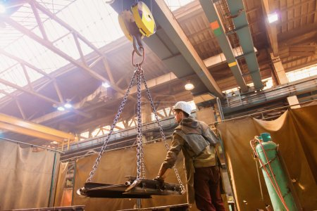 Photo for Young man in a factory preparing equipment for welding - Royalty Free Image