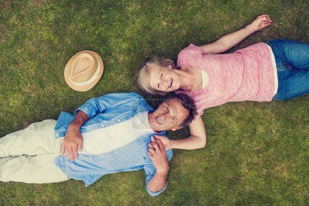 Senior couple lying on a grass and hugging