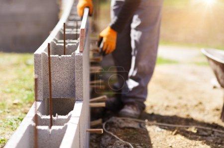 Bricklayer putting down row of bricks
