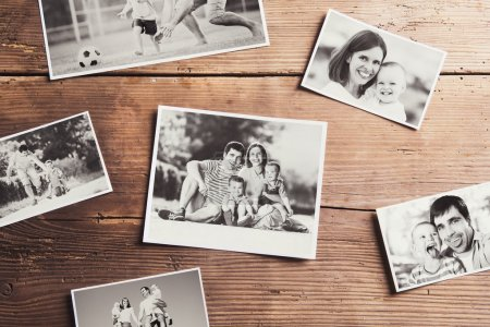 Photo for Black and white family photos laid on wooden floor background. - Royalty Free Image