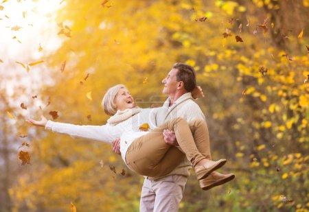 Photo pour Aînés actifs s'amuser et jouer avec les feuilles dans la forêt d'automne - image libre de droit