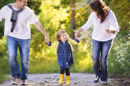 Photo for Happy young family spending time together outside in green nature - Royalty Free Image