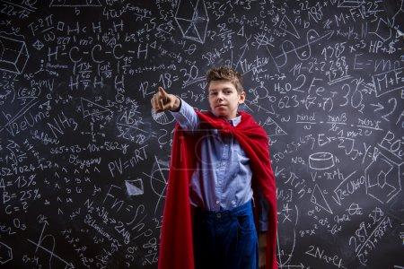Photo pour Jeune écolier beau avec une cape rouge devant le grand tableau noir - image libre de droit