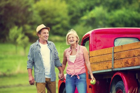 Photo for Senior couple standing next to the red truck - Royalty Free Image
