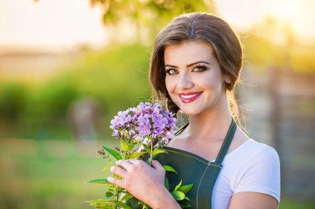 Photo pour Belle jeune femme jardinage extérieur dans la nature d'été - image libre de droit