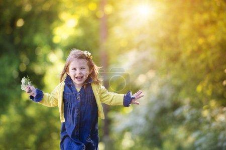 Photo pour Petite fille mignonne dehors dans la nature par une journée d'été ensoleillée - image libre de droit