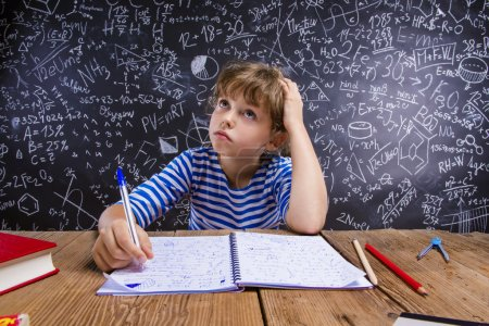 Photo pour Mignonne petite fille fait ses devoirs devant le grand tableau noir - image libre de droit