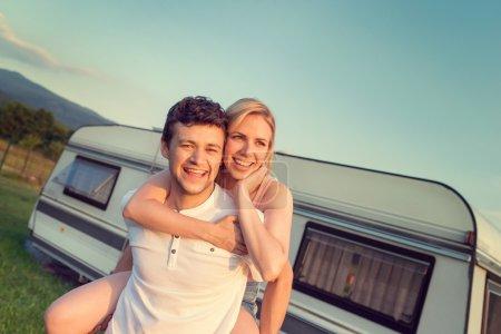 Photo pour Beau jeune couple devant un camping-car sur une journée d'été - image libre de droit
