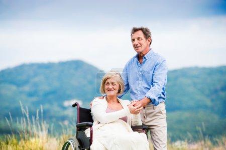 Photo pour Senior homme avec femme en fauteuil roulant à l'extérieur dans la nature - image libre de droit