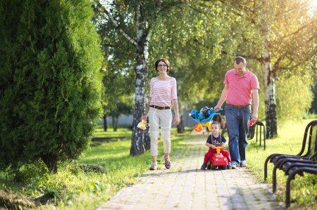 Photo pour Joyeux jeune famille marchant dans le parc pendant une journée d'été - image libre de droit