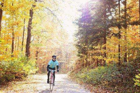 Photo pour Jeune beau sportif chevauchant son vélo à l'extérieur dans la nature ensoleillée d'automne - image libre de droit