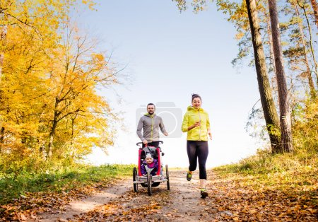Photo for Beautiful young family running outside in autumn nature - Royalty Free Image