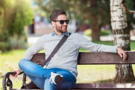 Photo for Handsome young man sitting on park bench - Royalty Free Image