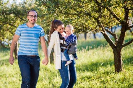 Photo pour Heureux jeune famille, passer du temps ensemble à l'extérieur dans la nature verdoyante - image libre de droit