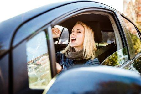 Photo pour Belle jeune femme blonde conduire une voiture et le chant - image libre de droit