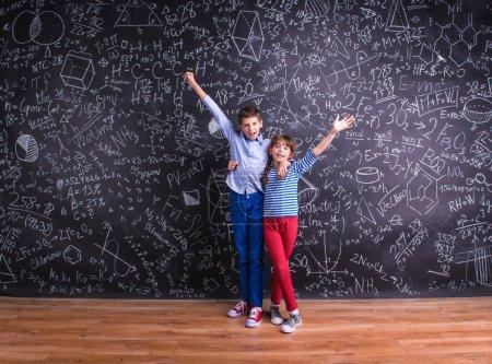 Photo pour Joli petit garçon et petite fille devant un grand tableau. Studio tourné sur fond noir - image libre de droit