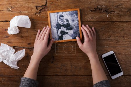 Photo for Unrecognizable woman holding broken picture of couple in love. Ended relationship. Crying.Valentines day composition. Studio shot on brown wooden background - Royalty Free Image
