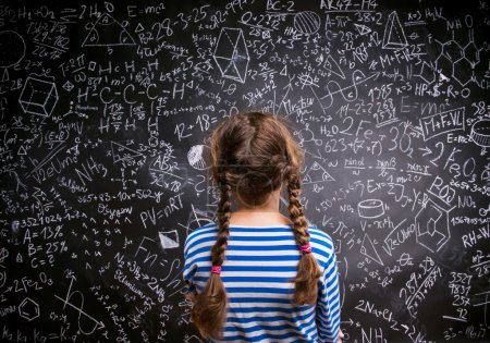 Photo for Girl  in blue striped t-shirt with two braids against big blackboard with mathematical symbols and formulas, back view, rear viewpoint - Royalty Free Image