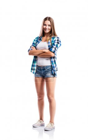 Photo for Standing teenage girl in denim shorts , tight singlet, blue checked shirt and canvas sneakers, arms crossed, young woman, isolated on white background - Royalty Free Image
