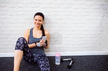 Photo pour Femme en forme attrayante souriante dans la salle de gym assis sur un plancher tenant le téléphone intelligent contre le mur de briques blanches, bouteille d'eau, poids - image libre de droit