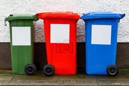 Photo pour Poubelles poubelle colorée alignés près du mur - image libre de droit
