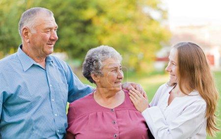 Photo pour Heureux couple âgé avec leur soignant dans la nature - image libre de droit