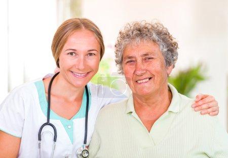 Photo pour Photo de heureuse femme âgée avec le jeune médecin - image libre de droit