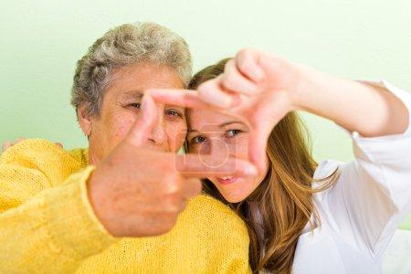 Photo pour Femme âgée et sa fille font cadre avec leurs doigts - image libre de droit