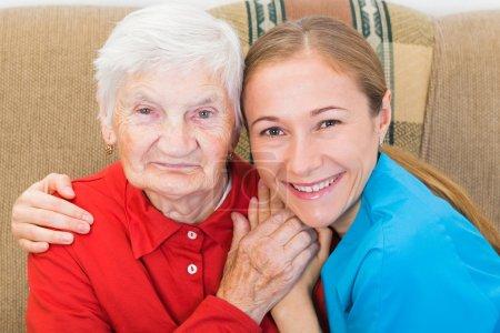 Photo pour Photo de la femme âgée avec le jeune soignant - image libre de droit