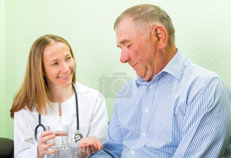 Photo pour Jeune médecin aidant l'homme âgé à prendre les pilules - image libre de droit