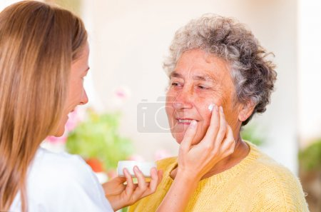 Caregiver rubs the face cream on the elderly woman...