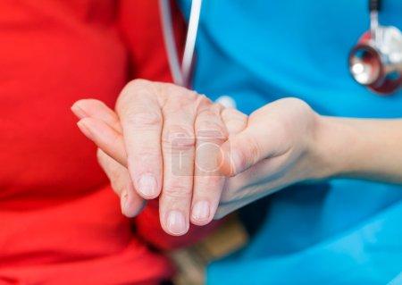 Photo pour Jeune médecin donner un coup de main pour femme âgée - image libre de droit
