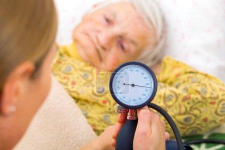 Photo pour Jeune médecin mesure la pression artérielle de la femme âgée - image libre de droit