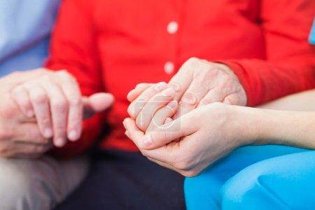 Photo pour Jeune soignant donnant la main pour aider les femmes âgées - image libre de droit