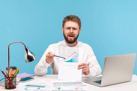 Photo pour Homme nerveux excité employé de bureau montrant du papier avec un diagramme, pointant vers une flèche croissante, inquiet de la forte hausse des prix. Studio intérieur tourné isolé sur fond bleu. - image libre de droit