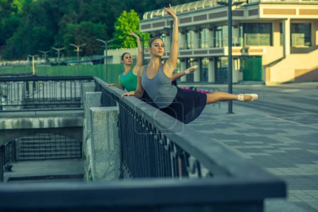 Photo pour Two young beautiful twin sister dancing ballet in the city with ballet costume. urban sync dance. Developed from RAW. retouched with special care and attention. - image libre de droit