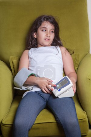 Small middle eastern girl feeling sick bad and holding digital blood pressure device.
