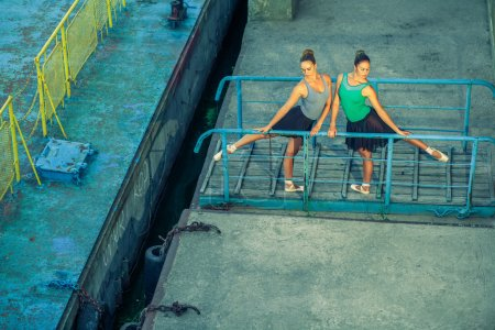 Photo pour Deux jeunes belles jumelles dansant le ballet dans la ville avec costume de ballet. danse de synchronisation urbaine. danse de rue industrielle. avec effet spécial. pose synchronisée. chaussures de ballet pointe et robe . - image libre de droit