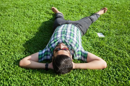 One fashion middle eastern man with beard, fashion hair style is resting on beautiful green grass day time. young arab businessman 20-30 years, resting after hard work. smart phone, tablet.
