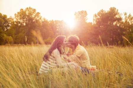 Photo pour Couple aimant couché sur le terrain floral dans le parc automnal, chaude journée ensoleillée, profiter de la famille, rendez-vous romantique, le bonheur et l'amour concept. embrasser et embrasser . - image libre de droit