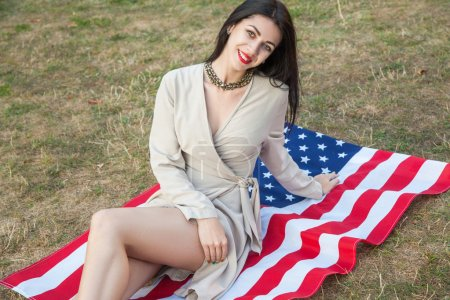 Beautiful sexy young woman with classic dress lying down on american flag in the park. fashion model holding us smiling and looking at camera. USA lifestyle with toothy smile.