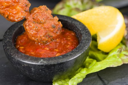 Photo for Spicy Chicken Satay - Marinated chicken meatball skewers served with chilli sauce and lemon wedges on a slate with reflections. - Royalty Free Image