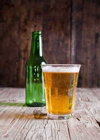 Photo pour Verre de bière et de bouteille d'isolement sur le fond rustique - image libre de droit
