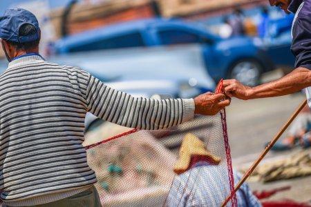 Photo pour Deux marins travaillant ensemble et en aidant les autres à s'étirer et de réparer le rouge filet de pêche - image libre de droit