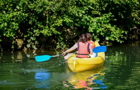 Two kids canoeing in a bautifull lake surrounded by green nature