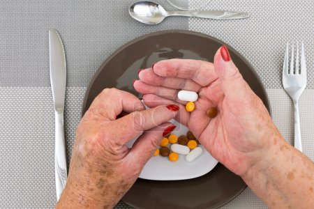 Red nailed elderly hands picking pills from a plate
