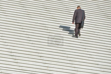 A man climbing up along large endless stair