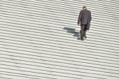 A man climbing up along large endless stair